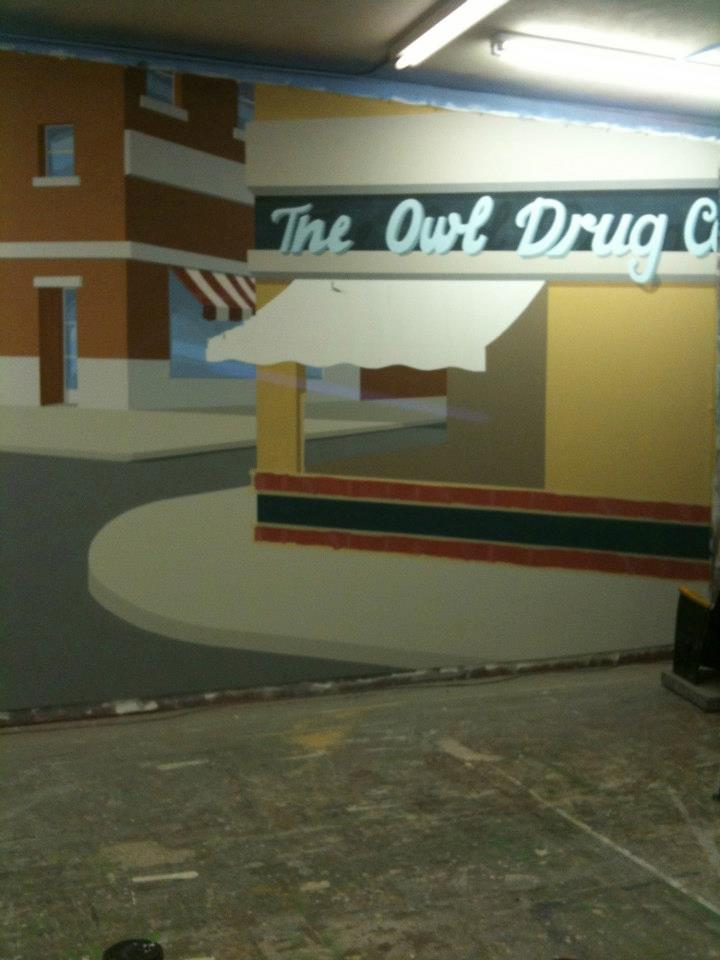 """This is day four- the side walls, street pavement, and shadows are blocked in. Also, the interior of the Drug Store gets a color and the red tile stripes are added."""